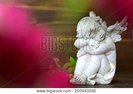 Angel guardian figurine sleeping on wooden background
