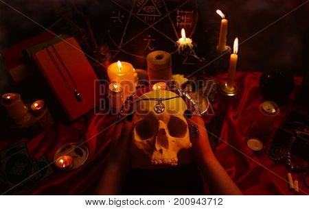 Witchcraft composition with witch's hands holding a human skull, candles, magic book, tarot cards, amulets and pentagram symbol. Halloween and occult concept, black magic ritual.