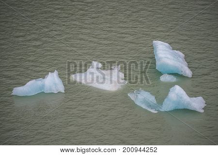 Blue ice floats in muddy water. Close-up. Pieces of ice float in the bay.