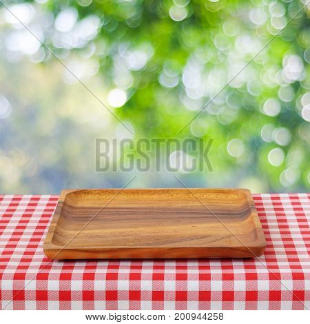 Empty wooden tray on table with red tablecloth over blur trees with bokeh background for food and product display montage