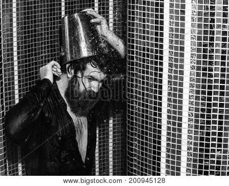 Cheerful handsome man bearded hipster with beard and moustache in red checkered shirt wet with water pours bucket of ice water on head in shower on colorful mosaic background