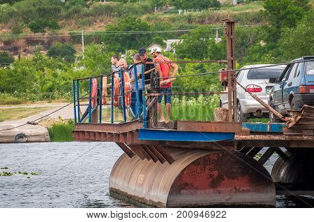 Ukraine Southern Bug River - 18 June 2017: Ferry crossing. The ferry moves with the help of a man's muscular strength. Repels from the steel cable. Such a ferry is unique in Ukraine.