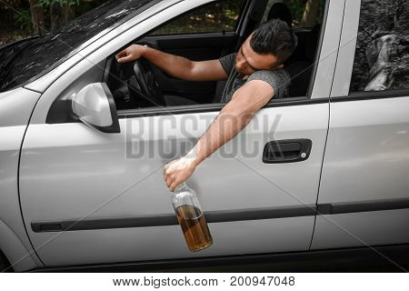 A drunk, boozed man driving a big gray car holding a bottle of beer. An alcoholic driving and drinking on a natural background. Accident on a road, illegal driving and alcohol abuse concept.