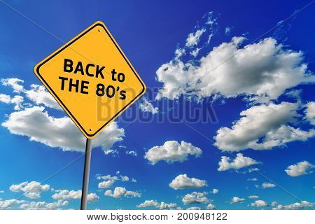 Background of blue sky with cumulus clouds and yellow road sign with text Back to The 80's