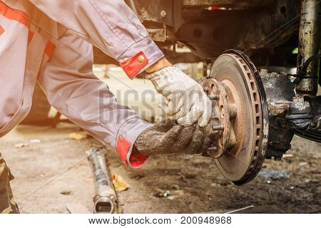 Technicians in grey uniform are repairing the brake of the car Automotive industry and garage concepts.