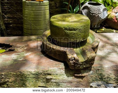 Ancient millstone have green lichen around and Ancient millstone put on old wooden boards. Behind the back green trees.
