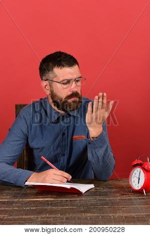retro clock and red book on vintage table. Man with interested face sits at wooden table. Teacher with beard looks at hand and writes in notebook on red background. Exam and studying concept