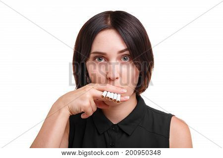 Close-up of a female nicotine addict smoking many cigarettes isolated on a white background. A beautiful, funny brunette girl with a stylish haircut in a black blouse, holding cigarettes.