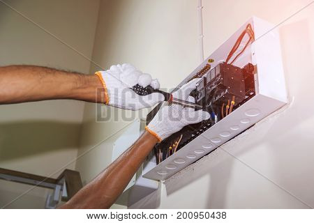 Close up of hand wearing gloves is using a screwdriver to tighten the circuit breaker to prevent power supply to the control box.