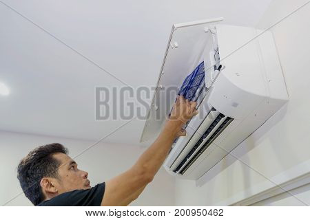 A man is removing the air filter of the air conditioner for cleaning.