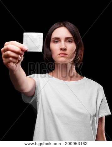 A young brunette woman showing a barrier device that reduces a sexually transmitted infection. Healthy lifestyle concept. Close-up of a serious female holding a packed condom on a black background.