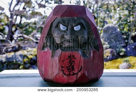 Traditional Japanese wooden Daruma monk idol with non-painted eyes on a background the Japanese garden