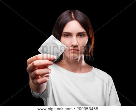 A portrait of a serious female holding a packed condom on a black background. A young brunette woman showing a barrier device that reduce a sexually transmitted infection. Healthy lifestyle concept.