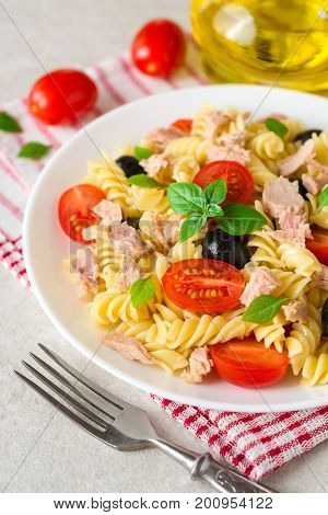 Fusilli Pasta Salad With Tuna, Tomatoes, Black Olives And Basil On Gray Stone Background
