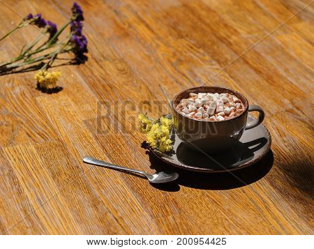 A close-up picture of a gray clay cup filled with hot cocoa drink and little white marshmallows. Warming beverage with flowers on a wooden table background. Cafe, breakfast, brunch concept.