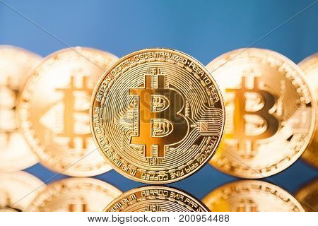 Five Virtual Coins Bitcoins On Blue Background