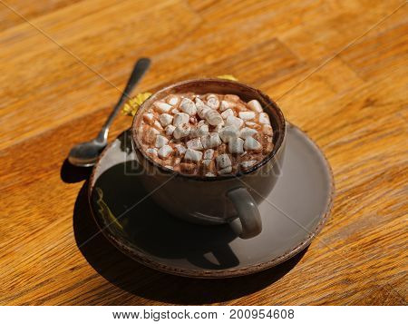 A view from above on a gray porcelain cup filled with hot cocoa drink and little white marshmallows. Warming beverage or hot coffee with flowers on a wooden table background. Breakfast, brunch concept