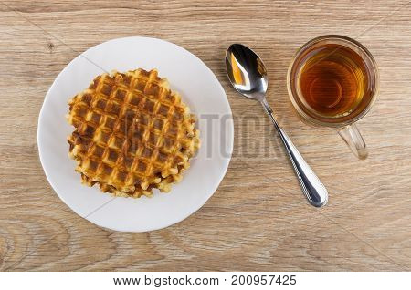 Round Waffles In White Plate, Cup Of Tea And Teaspoon
