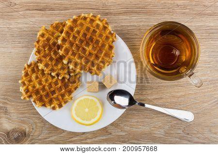 Round Waffles, Lemon, Sugar, Teaspoon In Plate And Tea