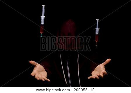 A narcomaniac guy in a dark red hoodie hallucinating in a drug overdose. Young man with drug syringes on a black background. Cocaine, meth, cannabis, LSD, ecstasy, morphine addiction concept.