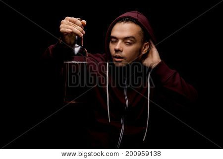 A boozed young man in a dark red hoodie holding a bottle of alcoholic beverage standing on the black background. A stressed, problematic, addicted male student with alcoholic intoxication.