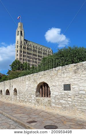 Wall of the long barrack of the Alamo Mission with the historic Emily Morgan Hotel in the background in downtown San Antonio Texas