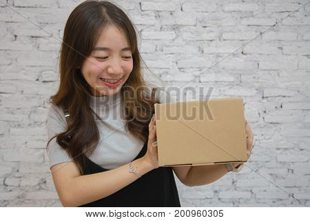Young asian woman smiling hold the box to send the customer, post, package and delivery concept, on white brick background