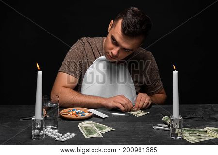 Drug-dependent teenager sitting at the table. A hopeless guy with a drug addiction on a black background. A young man in a T-shirt and a white bib. Drug traffic concept. Copy space.
