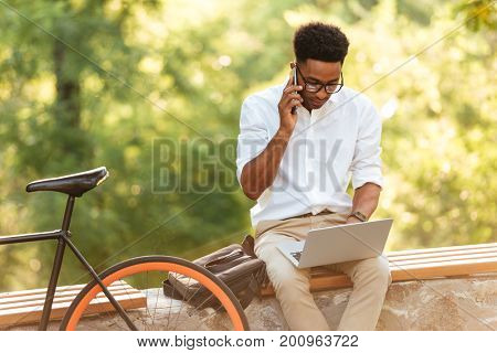 Image of young african handsome man early morning with bicycle outdoors. Looking aside using laptop computer. Talking by phone.