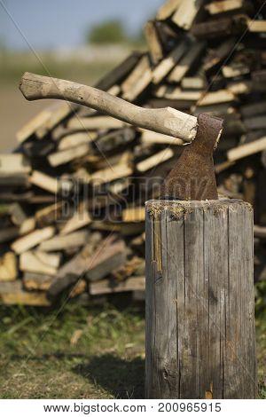 Old axe stuck in stump near woodpile, telephoto