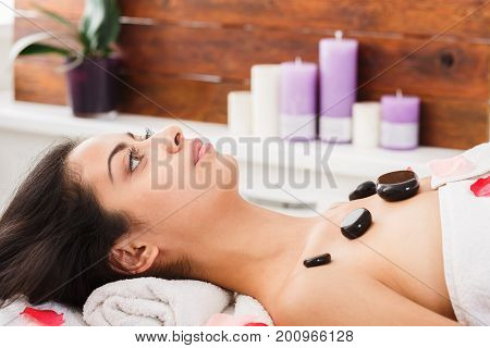 Relax in spa. Black marble stone massage in ayurvedic tradition. Beautiful girl in wellness center.
