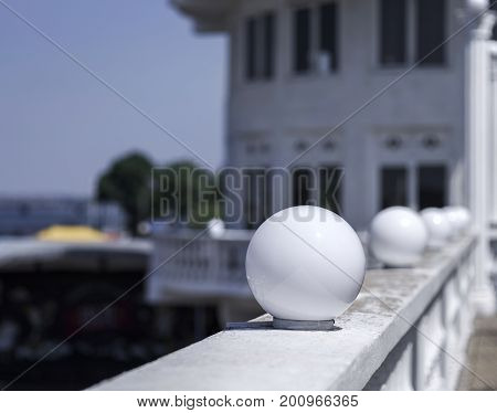 A close-up picture of a spherical white glass plafond street lights on a shabby white parapet. Round lanterns on a blurred white building background. Copy space. Outdoors concept.