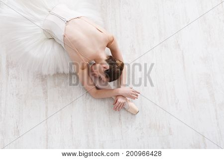 Graceful ballerina in pointe shoes at white wooden floor makes ballet leg stretching. Ballet practice of classical dancer, copy space