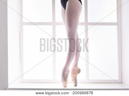 Beautiful ballerina legs in pointe at window background with copy space. Slim graceful feet of classical ballet dancer closeup, unrecognizable female.