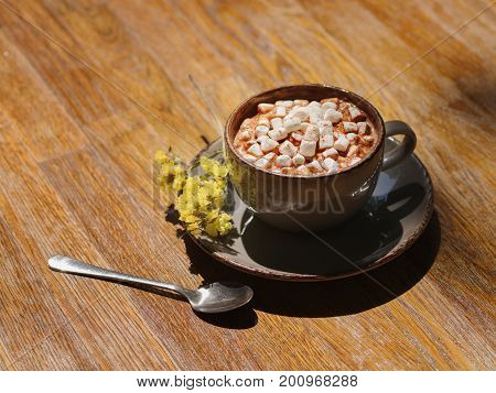 A close-up picture of a gray porcelain cup filled with hot cocoa drink and little white marshmallows. Warming beverage with flowers on a wooden table background. Cafe, breakfast, brunch concept.