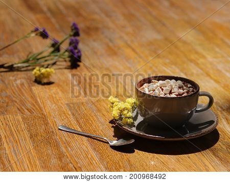 A close-up picture of a gray porcelain coffee cup filled with hot cappuccino and sugar white marshmallows. Sweet delicious beverage on a wooden table background. Cafe, breakfast, brunch concept.