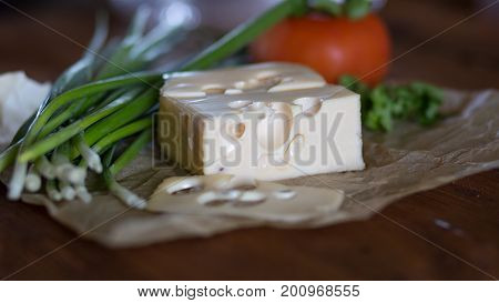 mouthwatering delicious piece of maasdam cheese and a slice on a wooden table surrounded by greenery and tomatoes