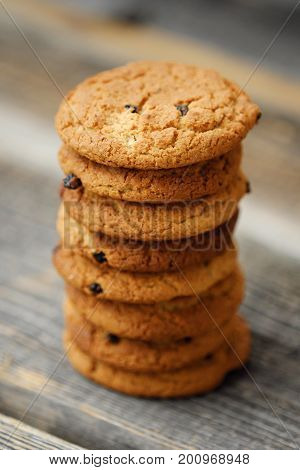 Homemade oatmeal cookies with raisins on wooden background