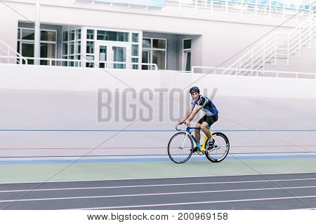 A young cyclist rides on a track in the open air. A man rides a bicycle on a cycle track