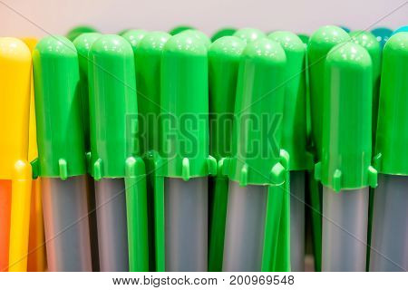 colorful pen caps on white and grey background