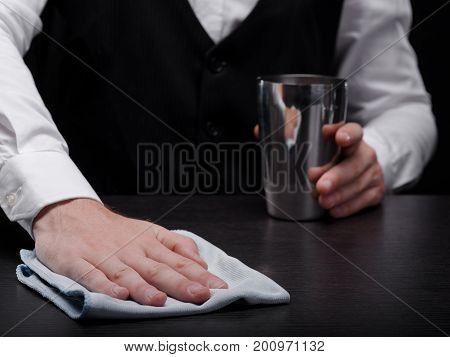 Close-up picture of bartender's hands cleaning a bar counter with a white handkerchief and holding a metal shiny shaker for mixes on the black background. A cleaning barman in a classic suit.