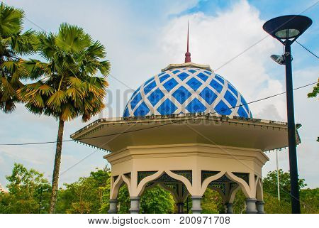 A Pavilion With A Blue Roof And Palm Trees On Sky Background. Miri City Fan Park, Borneo, Sarawak, M
