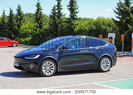 PAIMIO FINLAND - JULY 14 2017: Tesla Model X electric vehicle leaves Tesla Supercharger station. The Model X is an electric luxury crossover SUV manufactured by Tesla Inc.