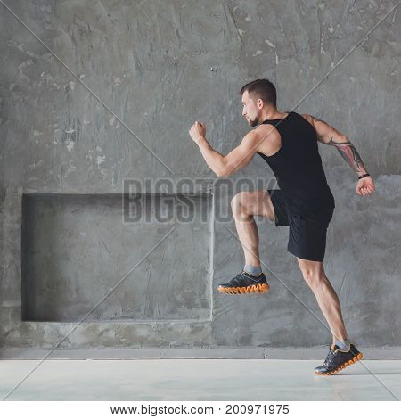 Workout. Male athlete sprinter running, exercising indoors, jogging in training room, side view, full length