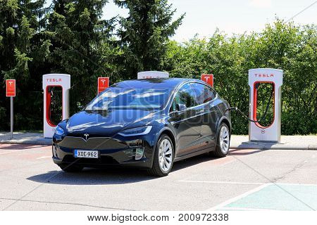 PAIMIO FINLAND - JULY 14 2017: Tesla Model X electric car is being charged at Tesla Supercharger station. The Model X is an electric luxury crossover SUV manufactured by Tesla Inc.