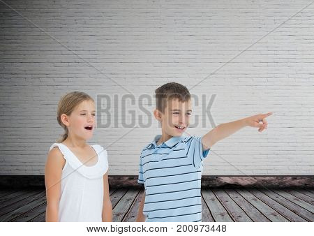Digital composite of kids pointing surprised with blank room background