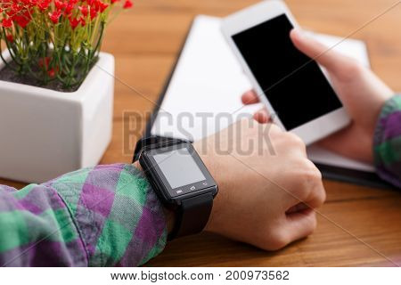 Male check smart watch and smartphone at workplace in office, shallow depth of field, close-up, copy space on the screen