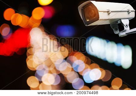 CCTV security camera system operating record and property protection with blurred image of street traffic light in the city at night vintage color tone surveillance security technology concept