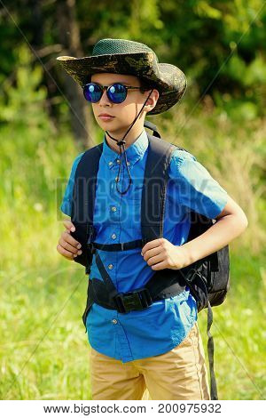 Ten year old boy go hiking with backpack. Exploring the world. Summer holidays. Outdoor activities.