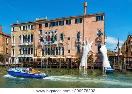 Venice, Italy - May 18, 2017: Giant hands rise from the water of the Grand Canal to support the building. This powerful report on climate change from the artist Lorenzo Quinn.